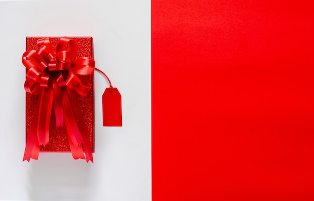 Rode kerstmisdoos met rood booglint en prijskaartje op wit en rood.