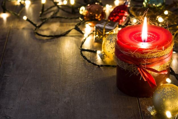 Rode kerstmiskaars en kerstmisornamenten op houten exemplaarruimte