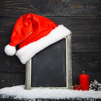 Rode kerstmuts op het bord met sneeuw
