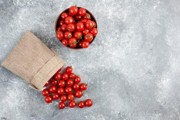 Rode kerstomaatjes uit een rustieke mand en in een houten beker op marmeren tafel.