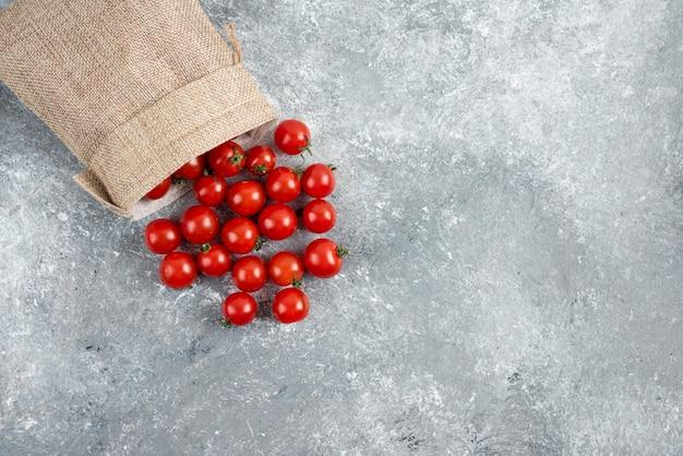 Rode kerstomaatjes uit een rustieke mand op marmeren tafel.