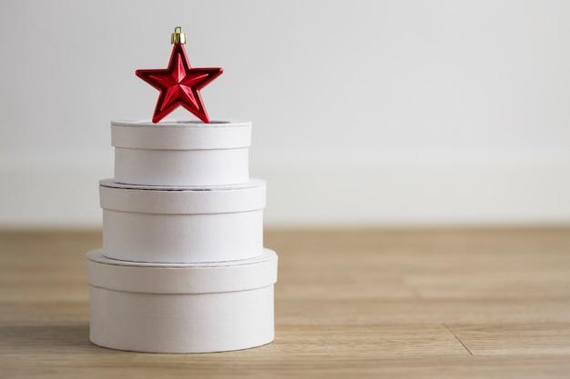 Rode kerstster over witte geschenkdozen met ongericht achtergrond