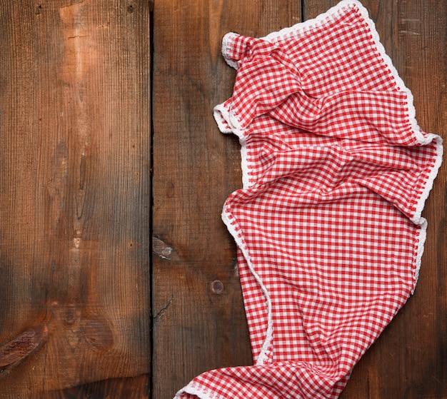 Rode keukenhanddoek op bruine houten achtergrond, bovenaanzicht, kopie ruimte