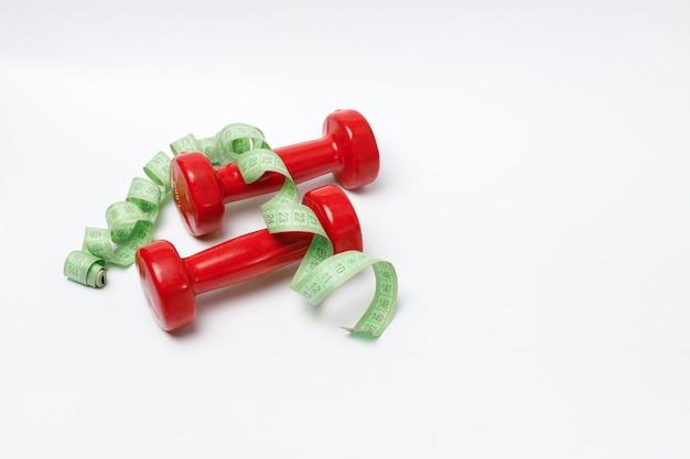 Rode kilogram dumbbells en meetlint op een witte achtergrond