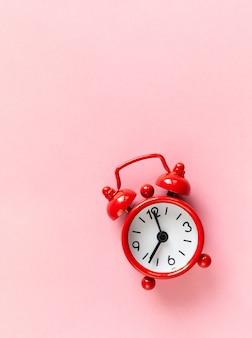 Rode kleine wekker op pastel roze achtergrond met copyspace.