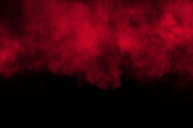 Rode kleur poeder explosie op zwarte achtergrond. rode stofdeeltjes spatten.