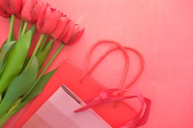 Rode kleur tulp bloem in een boodschappentas op rode achtergrond met kopie ruimte