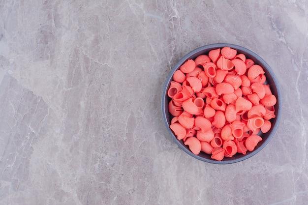 Rode kleurpasta's in een zwart metalen pan