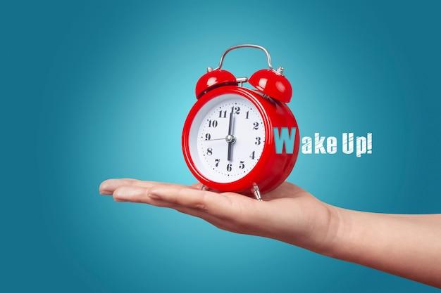 Rode klok met alarm bij de hand, wakker concept in de ochtend