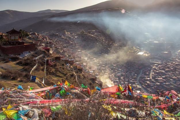 Rode klooster en thuis op larung gar (boeddhistische academie) in zonnige dag en is blauwe lucht