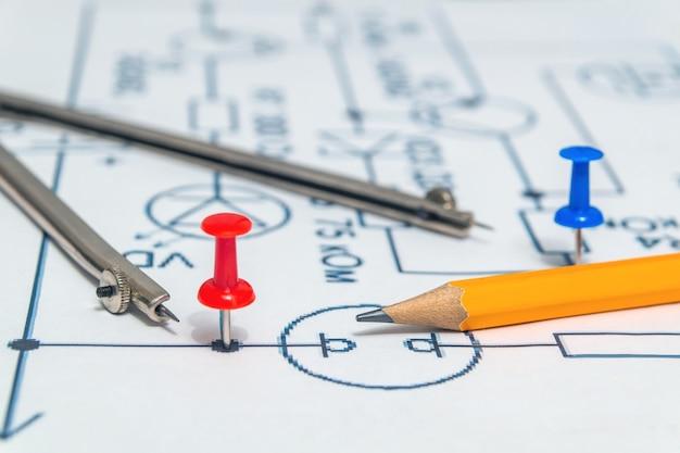 Rode knop en potlood op een elektrisch schema, werkomgeving