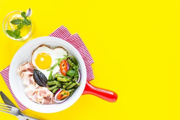 Rode koekenpan met heerlijk ontbijt op een gele, kopie ruimte. bovenaanzicht, selectieve aandacht.