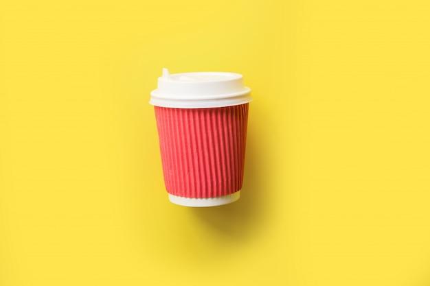 Rode koffie om document kop op gele achtergrond te gaan. plat leggen.