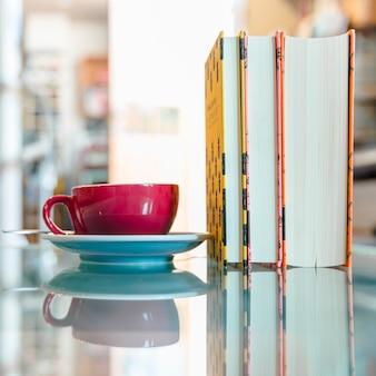 Rode koffiekop en boek op weerspiegelend glas