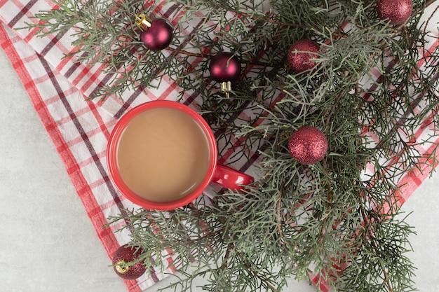 Rode koffiekop op tafelkleed met kerstballen en pijnboomtak
