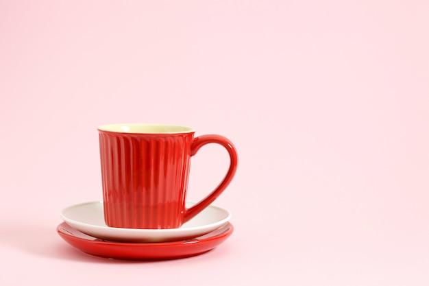 Rode koffiekop op witte en rode plaatpastelkleur over roze achtergrond.