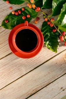 Rode koffiekopje met bladeren en koffie zaden op houten tafel top view