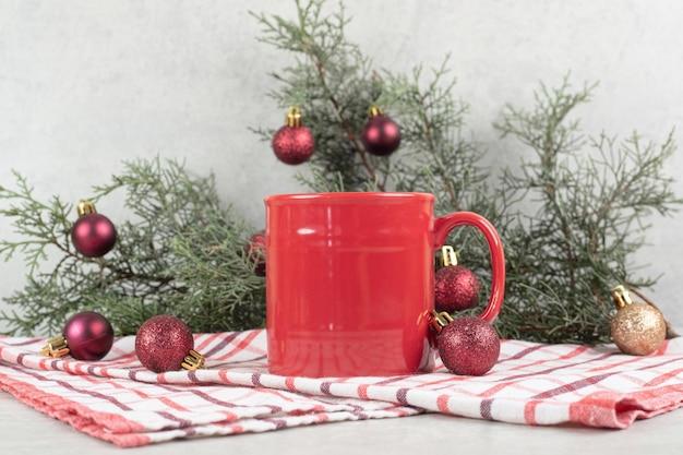 Rode koffiekopje op tafellaken met kerstballen en pijnboomtak.