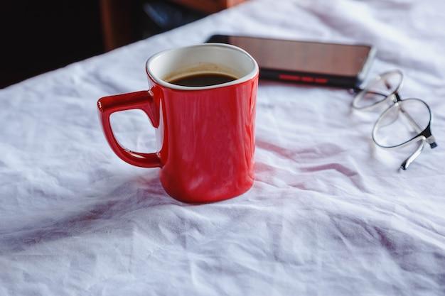 Rode koffiekopjes en glazen met een mobiele telefoon op tafel