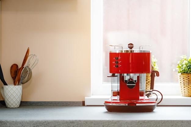 Rode koffiemachine op het aanrecht in de buurt van het vooraanzicht van het raam