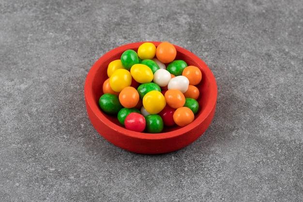 Rode kom met kleurrijke ronde snoepjes op stenen tafel.