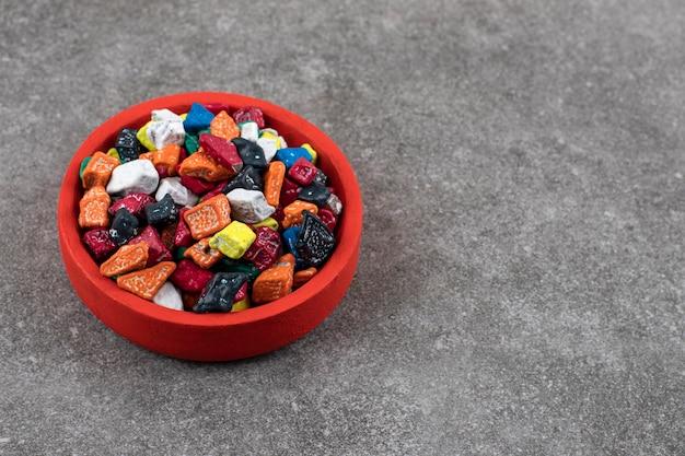 Rode kom met kleurrijke stenen snoepjes op stenen tafel.