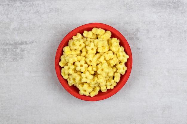 Rode kom vol heerlijke cornflakes op steen.