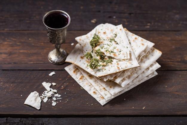 Rode koosjere wijn met een witte matzah of matza op een vintage houten muur gepresenteerd als een pascha seder maaltijd met kopie ruimte.