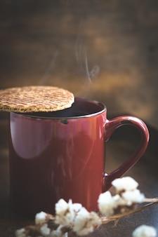Rode kop koffie met een stroopwafel over de kop. koffie rook, bokeh. kopie ruimte.
