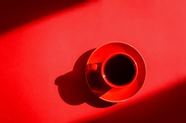 Rode kop koffie met schaduwen op rode achtergrond in natuurlijk zonlicht. minimalistische creatieve kunstcompositie. conceptueel beeld. eenvoudig visueel concept.