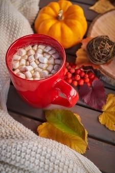 Rode kop met koffie en marshmallows. herfststemming, opwarmend drankje. gezellige sfeer, gele pompoenen