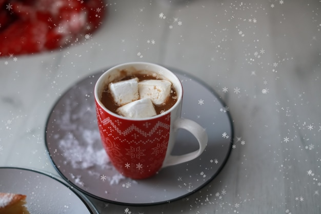 Rode kop met warme drank en marshmallow binnen