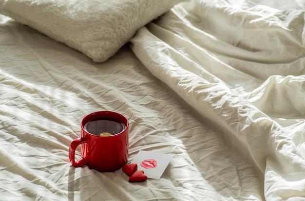 Rode kop thee en twee harten koekjes, een briefje met een kus op een wit bed