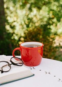Rode kop thee op tafel naast een boek en een bril in afwachting van de herfst