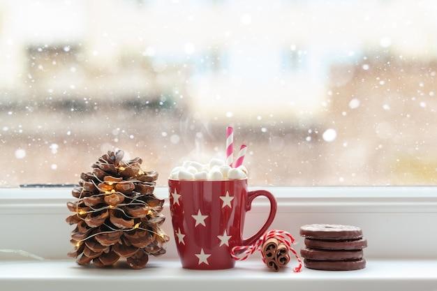 Rode kop warme chocolademelk of een chocoladedrank met marshmallows op de vensterbank