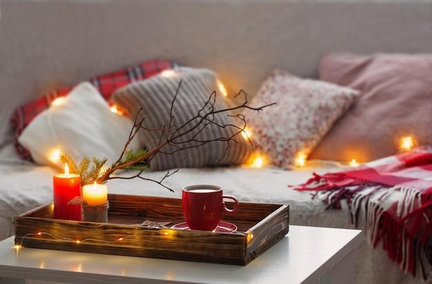 Rode kopje thee op dienblad met brandende kaarsen op achtergrondbank met kussens. gezellig huisconcept