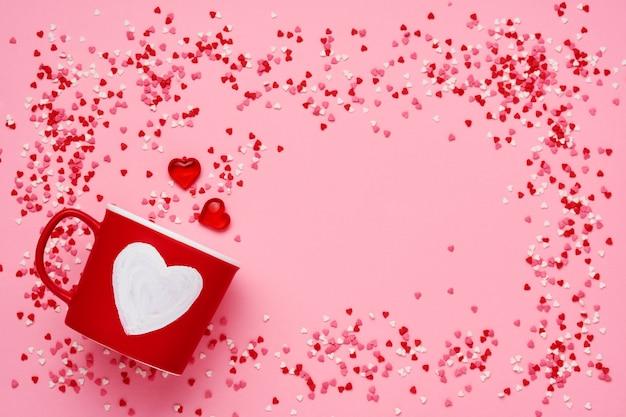 Rode kopmok met met geschilderde hart, suiker en chocoladeharten op roze lijst. plat lag samenstelling. valentijnsdag concept. bovenaanzicht, kopieer ruimte.