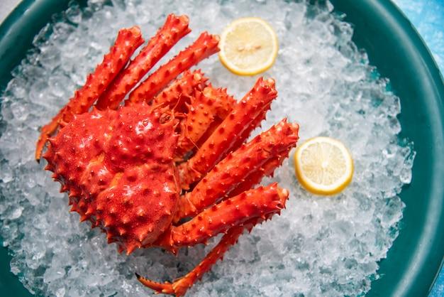 Rode krab hokkaido op ijs bij zeevruchtenmarkt. alaska king crab met citroen