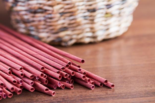 Rode krantenbuisjes voor het weven van kranten en het deel van de handgemaakte mand