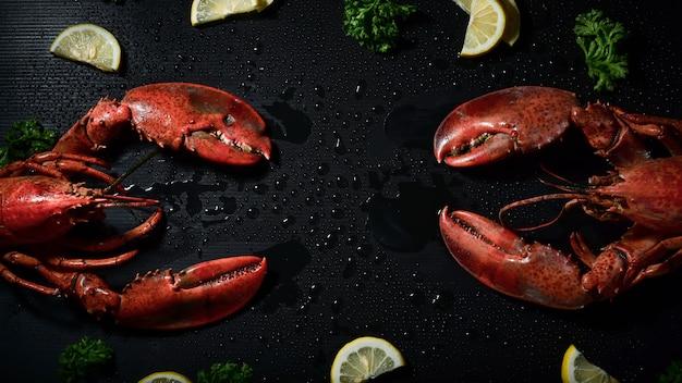 Rode kreeft met citroen en peterselie bovenaanzicht op zwarte achtergrond.