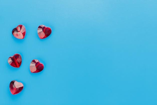 Rode kristallen op een blauw oppervlak in de vorm van een hart, jelly knapperige harten bovenop, uitzicht van bovenaf