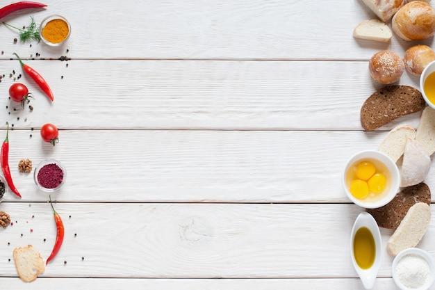 Rode kruiden en broodkader op witte houten vrije ruimte. bovenaanzicht op witte houten tafel met vers voedsel