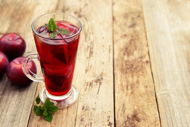 Rode kruiden- en fruitthee in glazen beker en thee met pruimen.