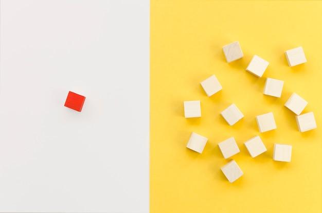 Rode kubus gescheiden van groep houten