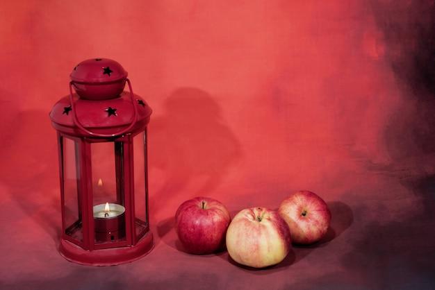 Rode lantaarnlamp met kaars en appels