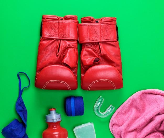 Rode lederen bokshandschoenen, een plastic waterfles en een roze handdoek en blauwe textielverband