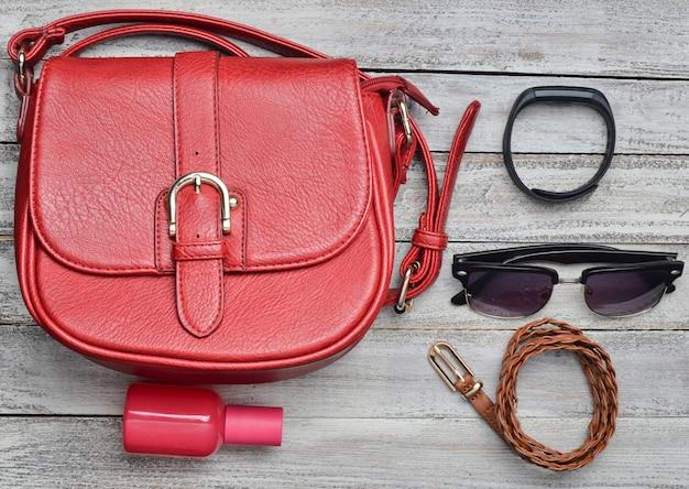 Rode lederen tas en andere vrouwelijke accessoires lay-out op een houten bureau. bovenaanzicht trend van minimalisme. plat leggen.