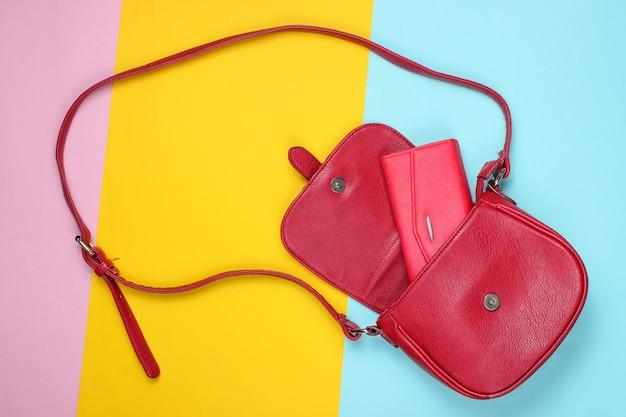 Rode lederen tas met tas op pastel gekleurde achtergrond.