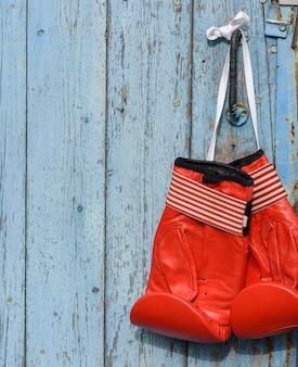 Rode leer bokshandschoenen die op een oude blauwe houten muur hangen