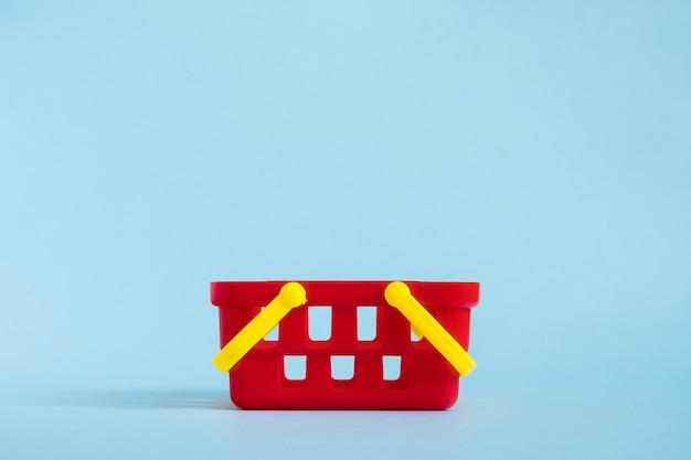 Rode lege stuk speelgoed plastic die boodschappenmand op blauwe achtergrond wordt geïsoleerd. verkoop en winkelen concept. kopieer ruimte